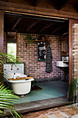 Vintage bathtub in front of a brick wall in a natural bathroom with a wide open sliding door