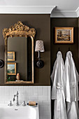 Gold frame mirror and umbrella wall lamp in a stylish bathroom with brown walls