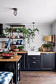 Kitchen with black fronts, white metro tiles and kitchen island