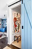 Wohnzimmer mit blauer Schiebetür zum Fernsehzimmer in umgebauter Garage