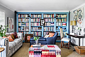 Living room in a mix of styles with a sky-blue bookcase, sofa, ottoman and upholstered table