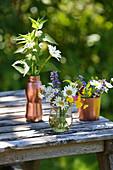 Wildblumensträußchen in Glasvase und kupferfarbenen Gefäßen