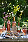 Baguette mit Blütenbutter auf Tisch dekoriert mit Wiesenblumen in kupferfarbenen Gefäßen