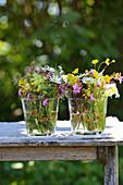 Mit Lackstiften dekorierte Glasgefäße für Wildblumensträußchen
