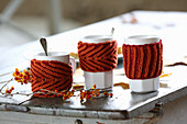 Rusty-red hand-knitted mug warmers for decorating autumnal table