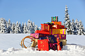 Gifts wrapped in brightly coloured paper on sledge in snow