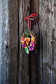Small willow wreath decorated with colourful felt flowers and felt hearts