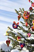 Fir tree in snowy landscape decorated with handmade felt pendants