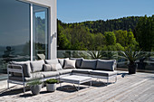 Outdoor couch on wooden desk of spacious roof terrace