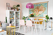 White table, bench and pink chairs below map decorating wall in dining area