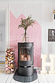 Attractive wood-burning stove against pink-and-white wall