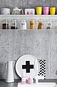 Storage jars and crockery on metal shelves on grey concrete kitchen wall