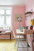 Desk in feminine room with pink walls and yellow carpet