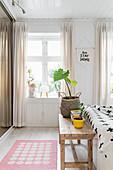 Wooden bedroom bench in bedroom in pale shades