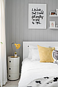Round drawer unit used as bedside table against grey wood-clad wall
