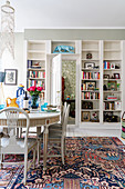 Stylish white dining table and fitted bookcase in bright interior