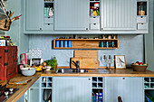 Pale blue cupboards and wooden worktops in Bohemian-style kitchen