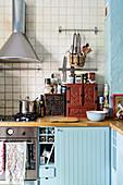 Küche im Boho-Stil mit Holzarbeitsplatten und hellblauen Schränken