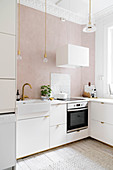 White fitted kitchen with stucco ceiling and powder-pink wall