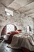 Layered bed linen on bed in old building with vaulted ceiling