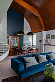 Blue velvet sofa, table in dining area and antique dresser below arched wooden ceiling