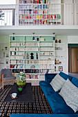 Velvet sofa and bookcase in living area of maisonette apartment