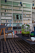 Bottle garden on black coffee table in front of bookcase with mint-green back wall