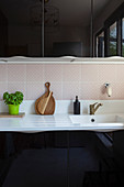 White sink in kitchen with black high-gloss cabinets and pale pink tiled splashback