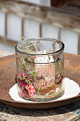 Glass candle lantern decorated with summer flowers, leaves and grasses