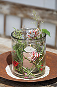 Candle lantern decorated with summery flowers, leaves and grasses