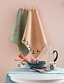 Printed tea towels hung from line against pink wall