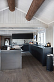 Modern, open-plan kitchen with exposed ceiling beams in rustic wooden house