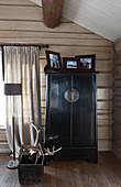 Black Chinese cabinet in rustic wooden house