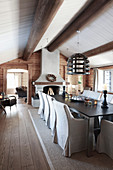 Open fireplace and exposed ceiling beams in rustic dining room