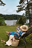 Woman sitting on lounger on lawn next to water