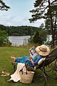 Frau auf einem Liegestuhl auf der Wiese am Gewässer