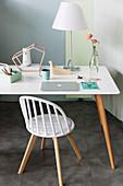 Schreibtisch mit weißer Tischplatte und Holzbeinen in Zimmerecke