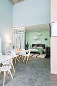 Loftwohnung mit Arbeitstischen und durch Vorhang abgetrenntem Schlafbereich