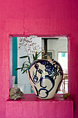 Blue-and-white vase in aperture in hot-pink wall