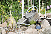 Water feature made from old watering can and succulents planted in boot