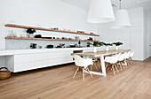 Lange, weiße Küchenzeile, darüber Holzregale, Esstisch mit Schalenstühlen