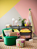 Colourful design: striped cushion on green armchair, floral pouffe and home accessories on shelves against three-tone wall