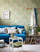 Floral design: blue sofa with scatter cushions against floral wallpaper
