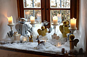 Handmade Christmas angels and candles surrounded by cotton-wool snow on windowsill