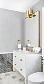 Bathroom washstand with marble top and brass fittings below mirror and wall lamps