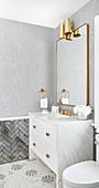 Waschtisch mit Marmorplatte und Messing-Armatur, darüber Spiegel und Wandleuchte, sechseckigen Marmorfliesen auf dem Boden
