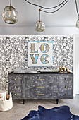 Nursery with rabbit wallpaper and 'Love' motto on wall above grey dresser