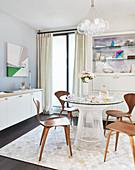 Runder Tisch mit Glasplatte und Stühle vor Anrichte im Esszimmer