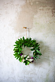 Wreath of lilac and lily-of-the-valley leaves on wall