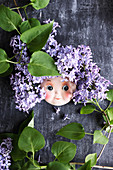Doll's face surrounded by purple lilac